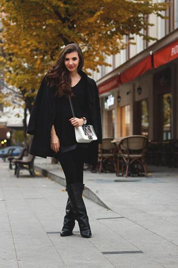 Девушка в сапогах, короткой юбке и черном пальто