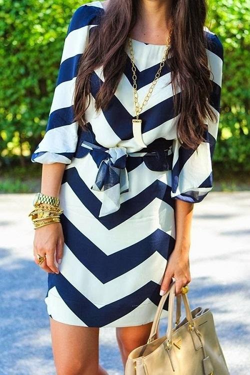 Девушка в сине-белом платье и золотистыми акчессуарами в морском стиле