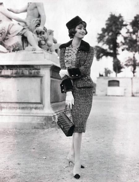 Девушка в теплом костюме с юбкой карандаш, жакет с меховым воротничком и черная сумочка