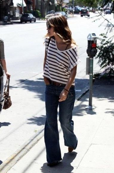 Девушка в топе в полоску и джинсах клеш