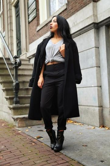 Девушка в укорченных брюках, ботильонах и черном пальто