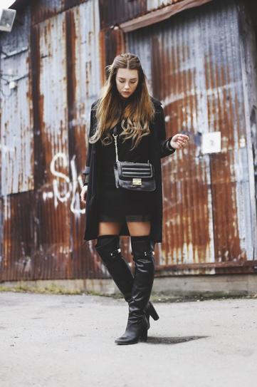 Девушка в высоких сапогах, коротких шортах и черном пальто