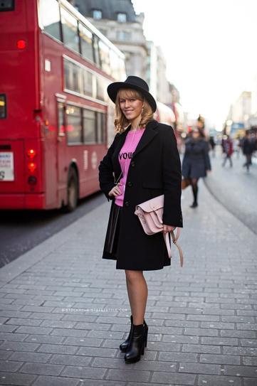 Девушка в юбке плиссе, розоавом топе, черном пальто и шляпе