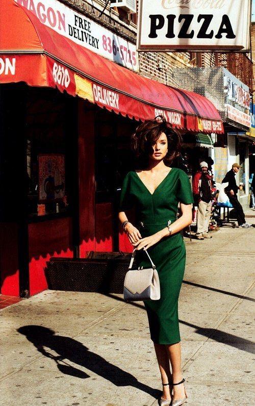 Девушка в зеленом платье-карандаш в треугольным вырезом и белая сумочка