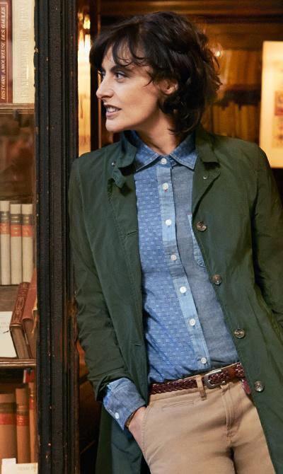 Инес Де Ла Фрессанж в бежевых брюках, голубой рубашке и плаще болотного цвета