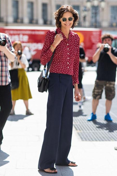 Инес Де Ла Фрессанж в черных прямых брюках и бордовой рубашке с белым принтом