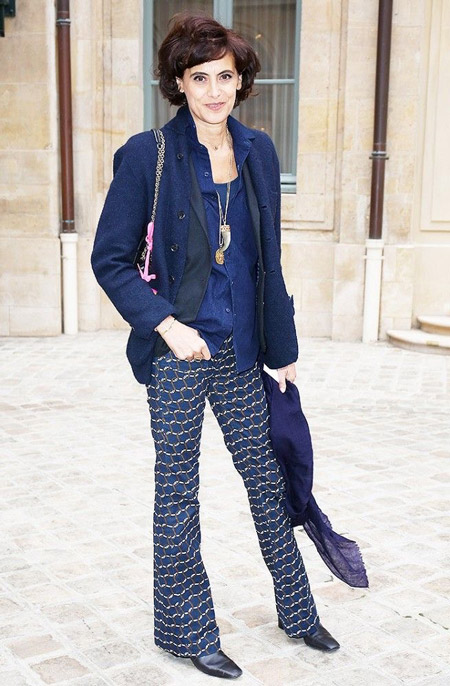 Инес Де Ла Фрессанж в расклешенных брюках с узором, синей рубашке и синяя кофта на пуговицах