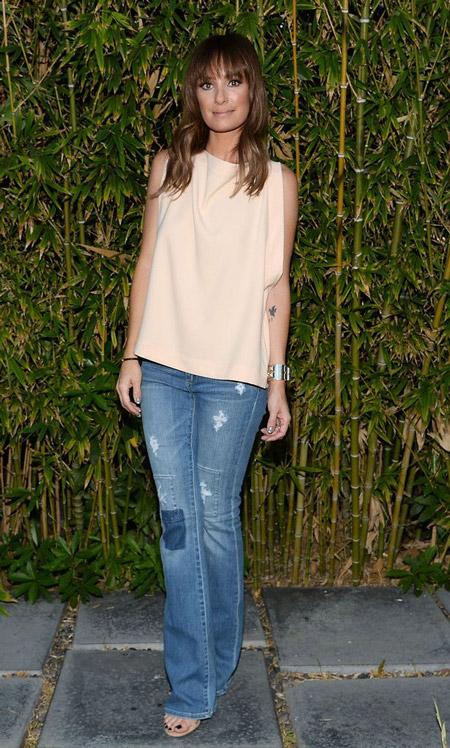 Катт Садлер в синих джинсах с заплатами и свободном топе