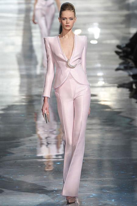 Модель в атласном брючном костюме с жакетом с треугольным вырезом