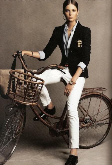 Модель в белых брюках, голубая рубашка и темный жакет, украшенный брошью