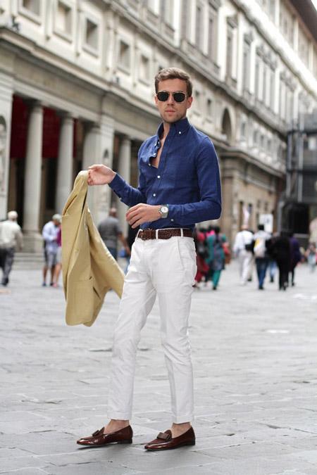 Модель в белых брюках с коричневым ремнем, синяя рубашка и пиджак
