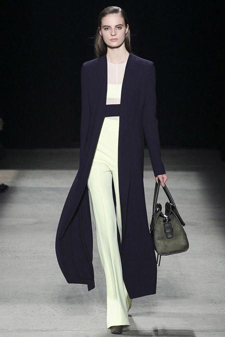 Модель в белых расклешенных брюках со стрелками и длинное черное пальто