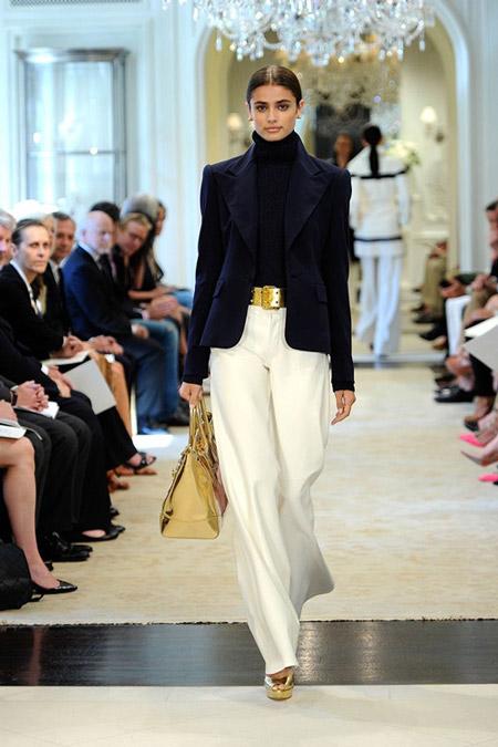 Модель в белых широких брюках, черная водолазка и приталенный жакет