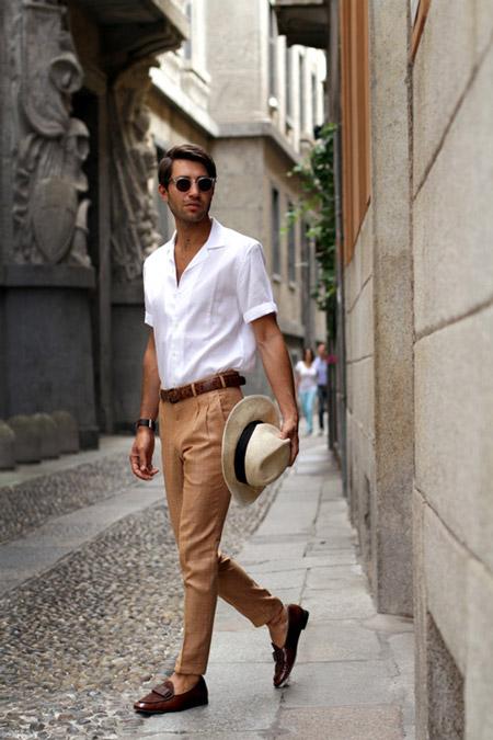 Модель в бежевых узких брюках и белой рубашке с короткими рукавами
