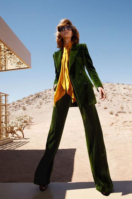 Модель в брючном костюме зеленого цвета с ярком желто оранжевым платком