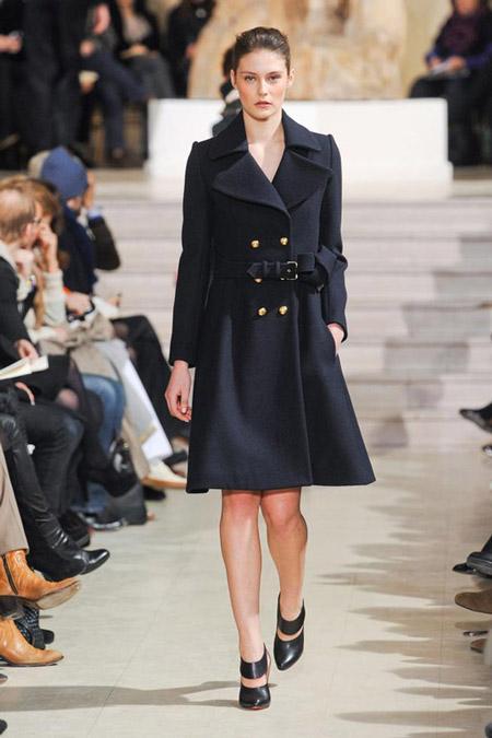 Модель в черном пальто с золотыми пуговицами и ремнем