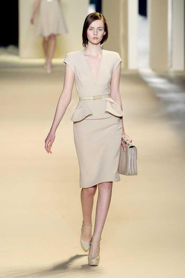 Модель в платье молочного цвета с баской и глубоким треугольным вырезом