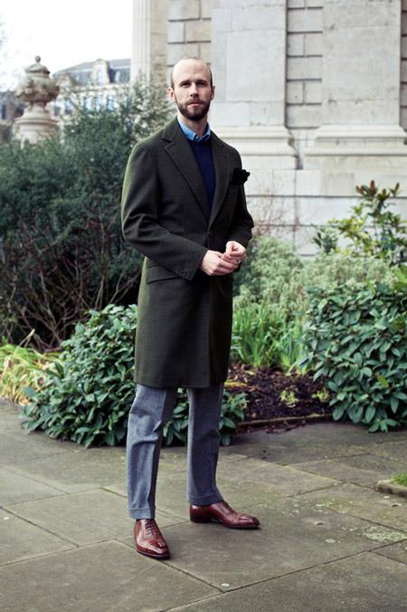 Модель в серых брюках со стрелками, синий жилет т удлиненное пальто