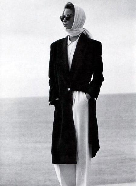 Модель в широких белых брюках и блузе, сверху черное длинное пальто