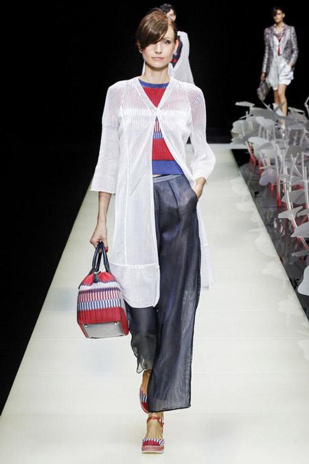 Модель в широких серых брюках, красно-синяя кофточка и белый удлиненный кардиган