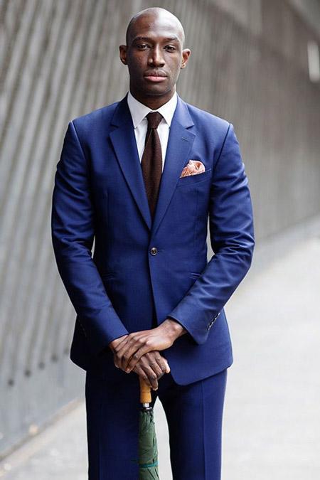 Модель в синем костюме с приталенным пиджаком, белая рубашка и галстук