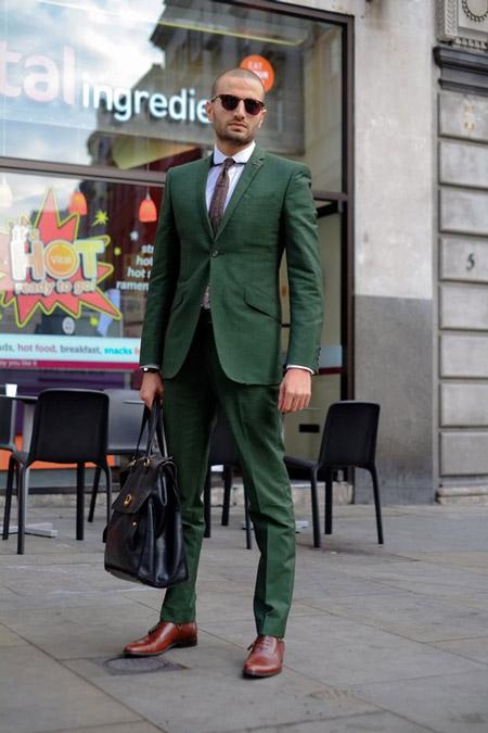 Модель в зеленом костюме, белой рубашкой, лалстук, большая кожанная сумка