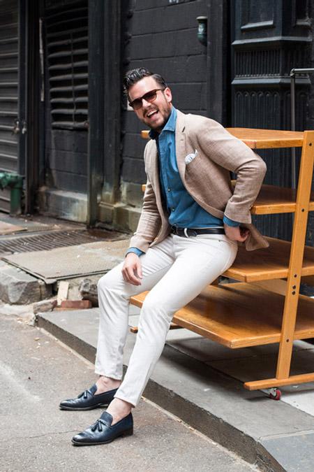 Молодой человек в белых брюках, синяя рубашка и светлый пиджак