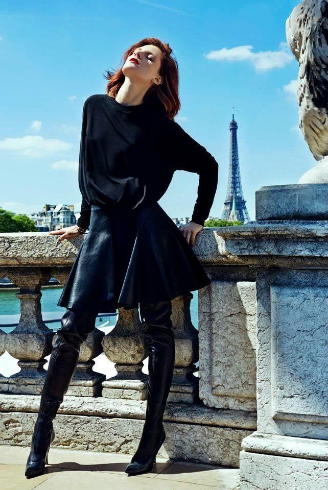 На девушке черные высокие сапоги, кожанная юбка-солнце и свиншот