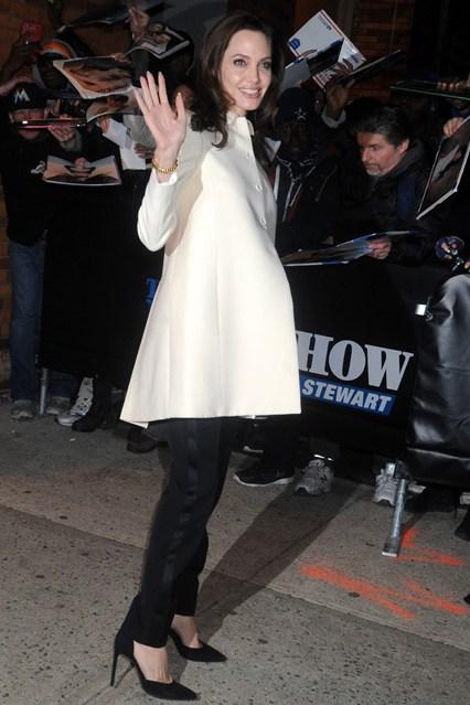 Анджелина Джоли в белом пальто и черных брюках