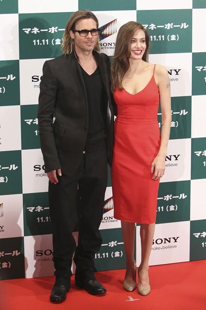 Анджелина Джоли в красном платье классического кроя от Versace, рядом Бред Питт
