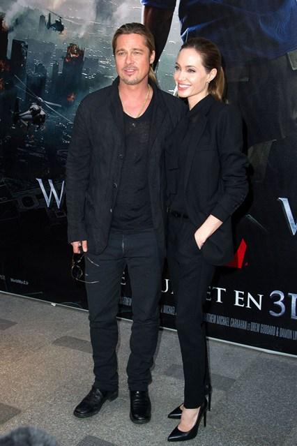 Анджелина Джоли в очень элегантном образе с черными брюками, пиджаком и топом от Saint Laurent, рядом Бред Питт