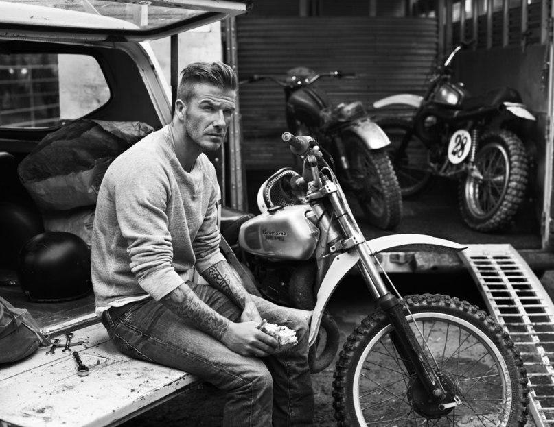 Дэвид Бекхэм в джинсах рядом с мотоциклом