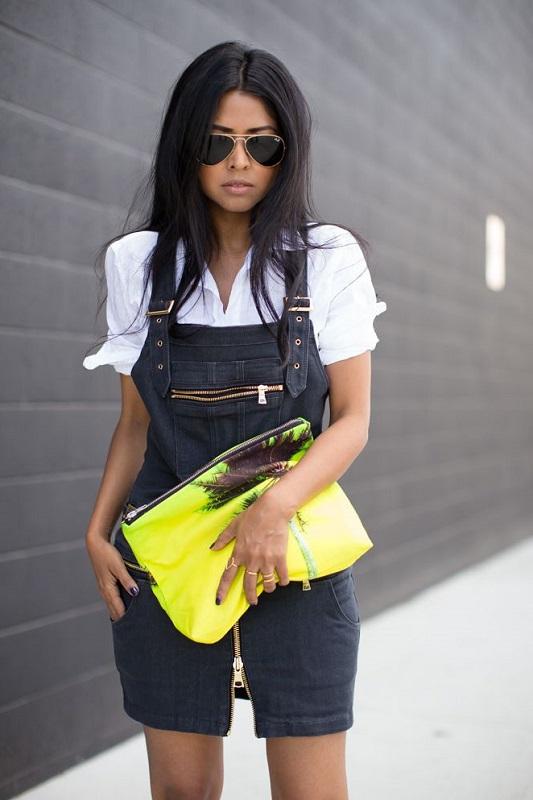 Девушка в темном, джинсовом комбинезоне, белой блузе и яркой, неоновой сумкой