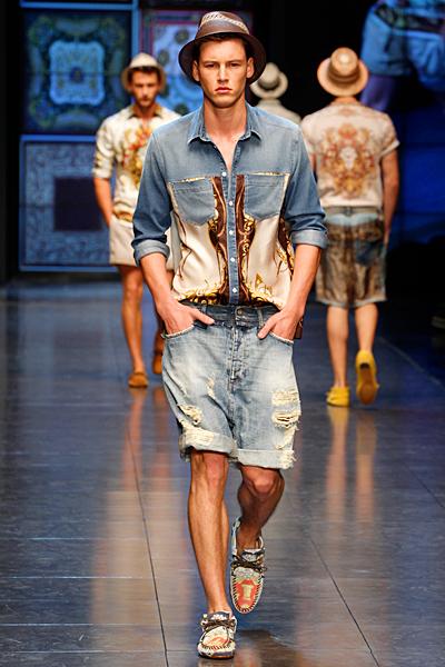 Модель в джинсовых шортах, джинсовой рубашке и шляпе идет по подиуму