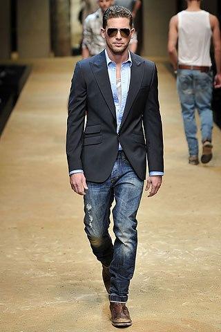 Парень в потертых, рваных джинсах и пиджаке идет по подиуму