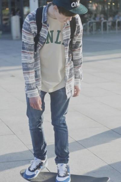 Парень в свободных джинсах, футболке и толстовке едет на скейте