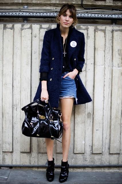 Алекса Чанг в джинсовых шортах с бахромой, черной блузе и синем пальто. Неизменно она выбирает черные ботильоны и сумку от Mulberry