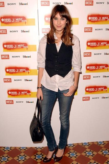 Алекса одета в черную жилетку, джинсы скинни и белую рубашку мужского кроя