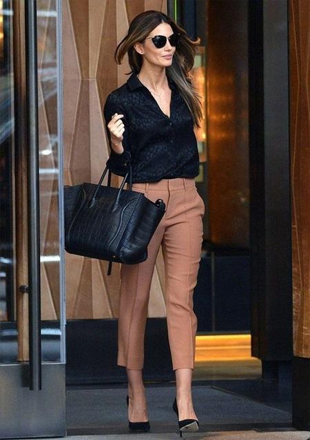 Девушка в черной блузке и бежевых брюках