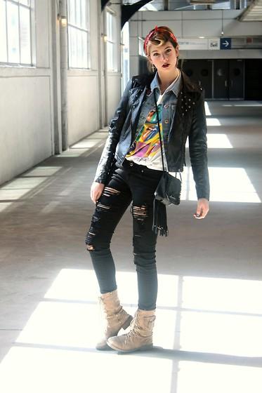 Девушка в черных рваных джинсах и ботинках