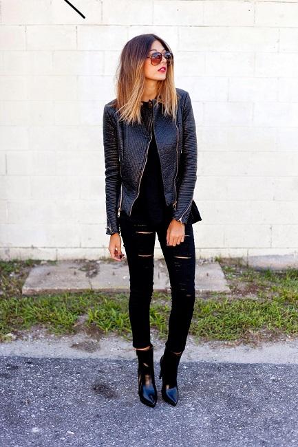 Девушка в черных рваных джинсах скинни