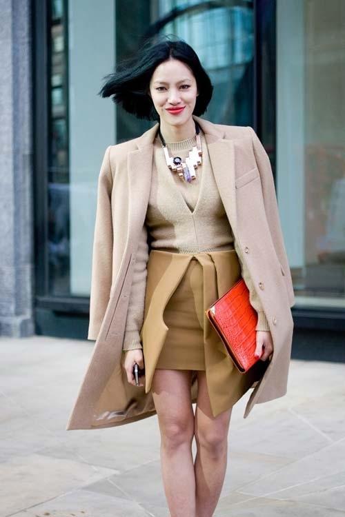 Девушка в мини юбке, пальто и крупным ожерельем на шее