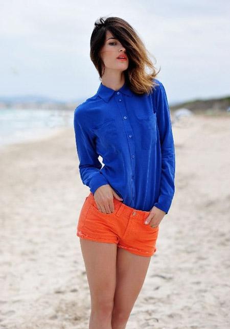 Девушка в оранжевых шортах и синей блузке