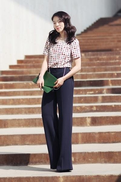 Девушка в широких, элегантных брюках и блузе с принтом