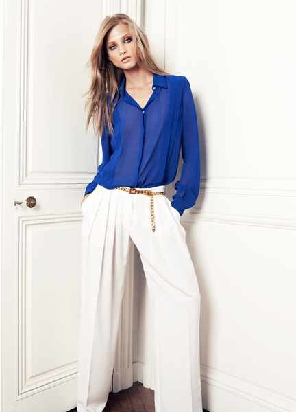 Девушка в синей блузке и белых брюках
