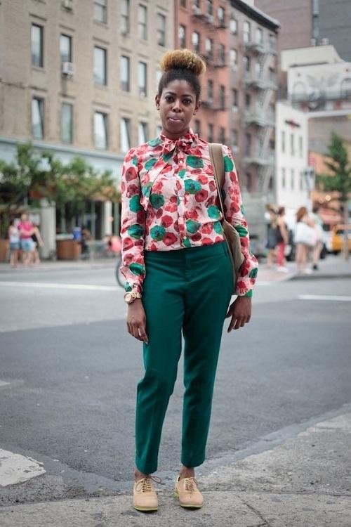 Девушка в зеленых брюках, блузе с принтом и удобных туфлях