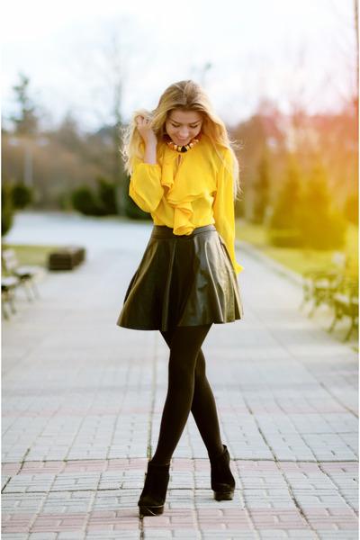 Девушка в желтой блузке и черной кожаной юбке