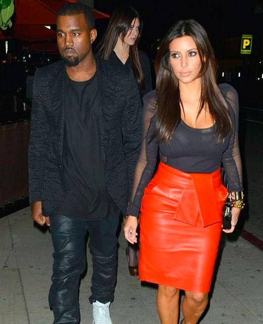 Ким Кардашьян в черной блузке и красной юбке с Кани Уэстом