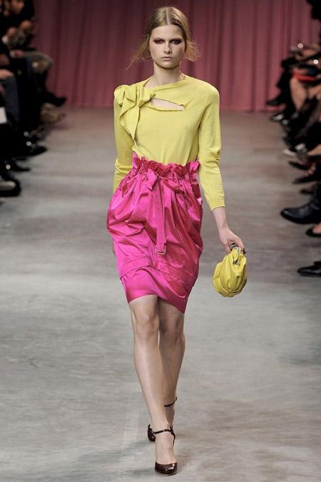 Модель в желтой блузке и розовой юбке