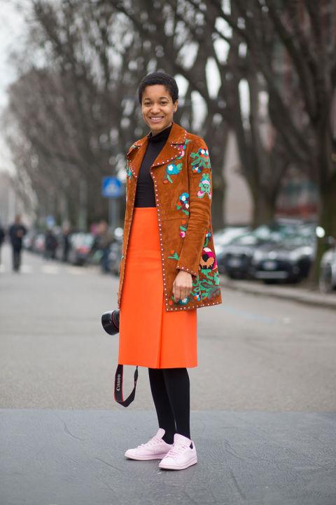 В этом образе сразу несколько трендов. Ярчайший оранжевый цвет и кроссовки в сочетании с юбкой и пальто